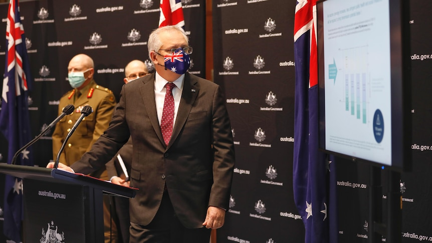 The Prime Minister, wearing an Australian flag mask, presents a powerpoint slide.