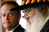 Tight photo of heads - Bill Shorten, out of focus, listens to Pat Dodson speak.