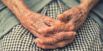An elderly person's hands folded