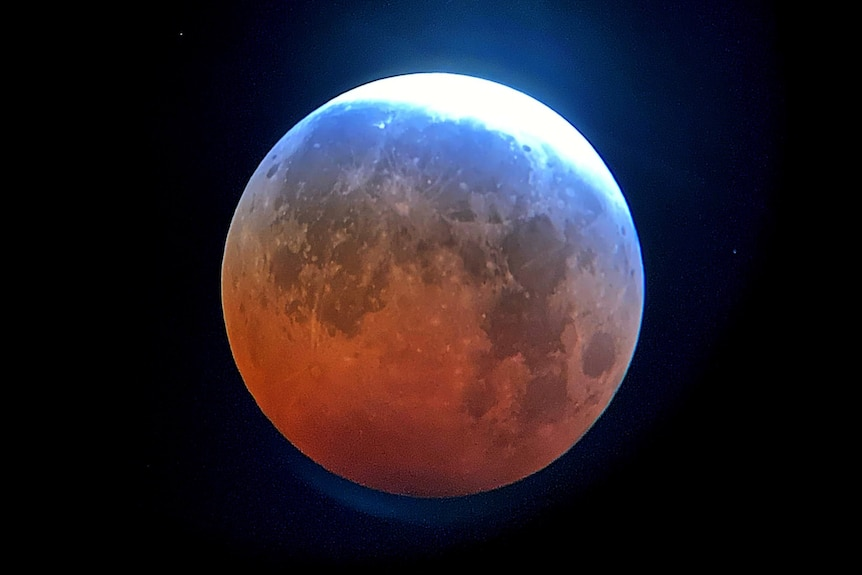 A red moon with a whitish halo.