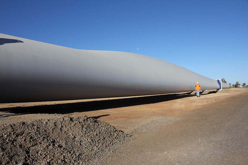 A wind turbine blade lying on the ground waiting to be installed.