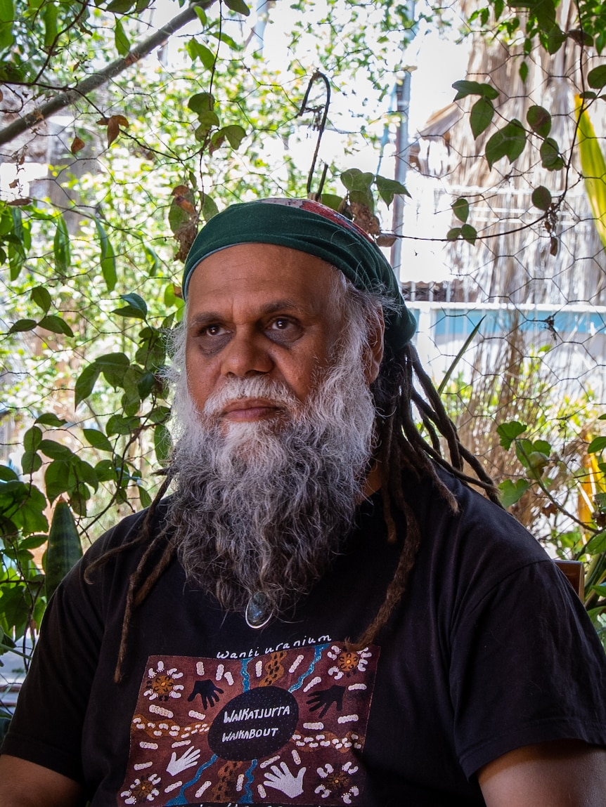 Portrait of an older Indigenous Australian man with a grey beard, a headband and dreadlocks.