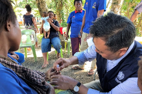A woman holds a baby as it is given the polio vaccine in PNG