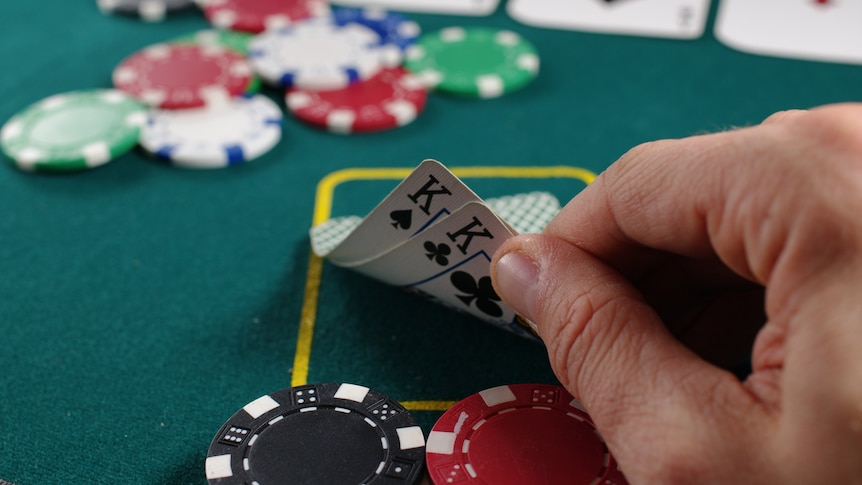 Close-up of a hand lifting two cards with coloured poker chips behind it, on a green felt surface.