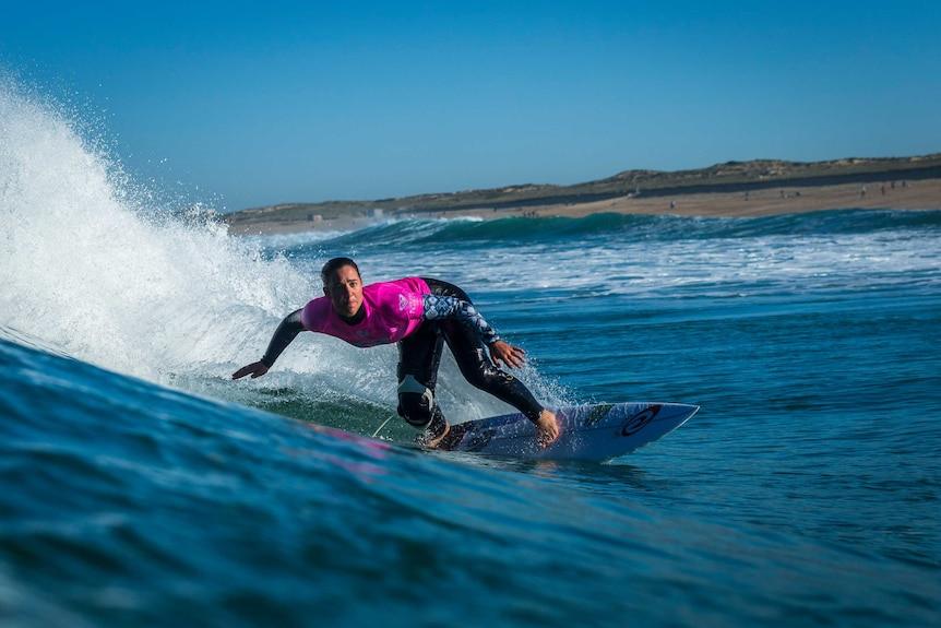 Action image of surfer making a turn on a wave with the shoreline in the background.