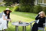 Dark-haired woman dressed in white sits in garden with older blonde-haired women dressed in black