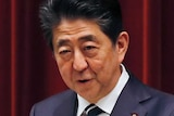 In front of a red curtain, Shinzo Abe speaks on a wooden lectern next two a stone plinth carrying framed Chinese characters.