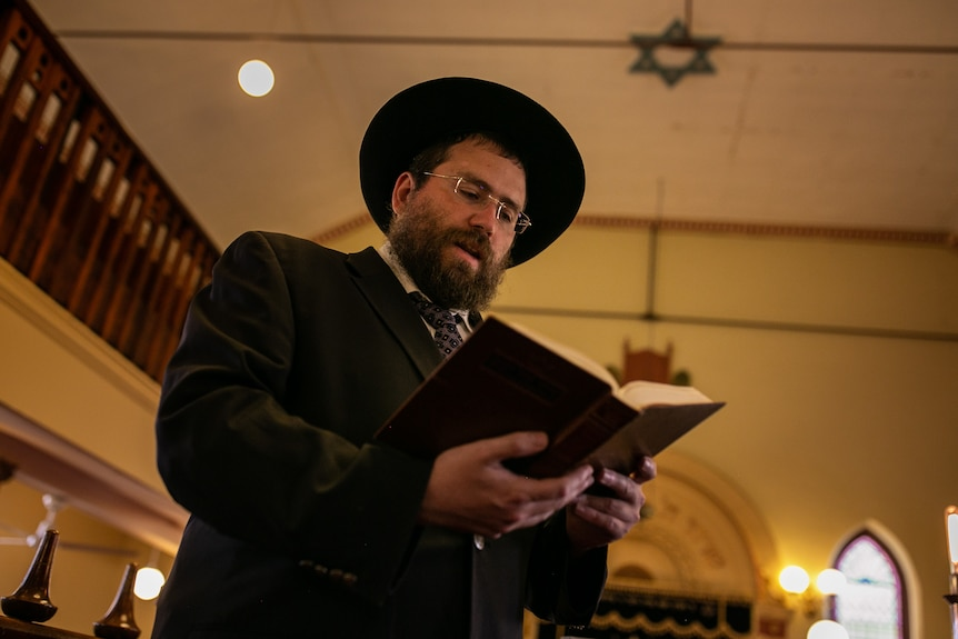 A man wearing a hat reads from a book in a synagogue.