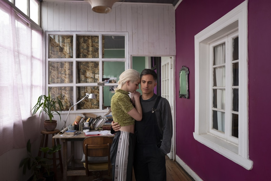 Film still of Mariana Di Girólamo as Ema and Gabriel García Bernal as Gastón in overalls holding each other at home in Ema