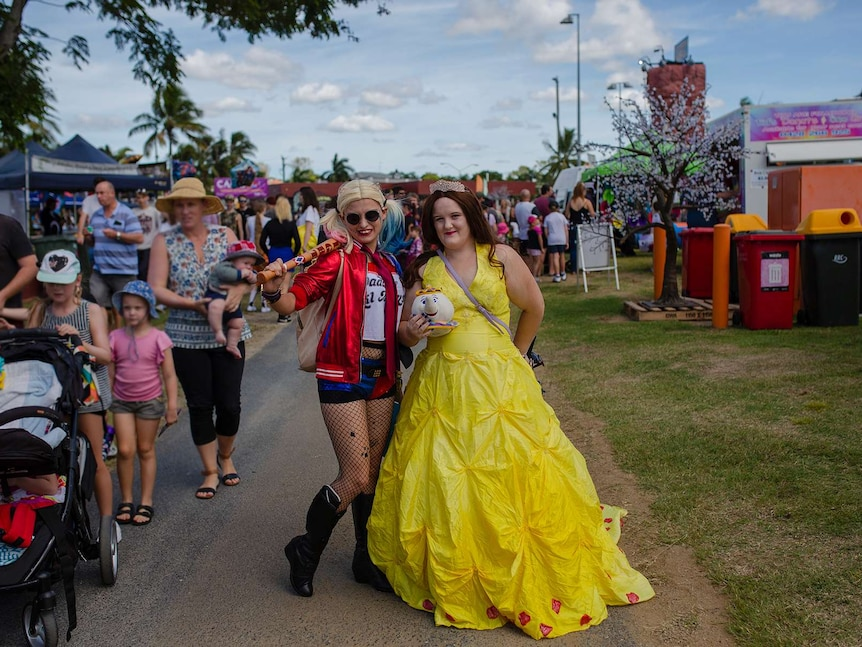 A woman stands with a baseball bat over her shoulder, dressed as Harley Quinn. Another stands next to her in a yellow ball gown.