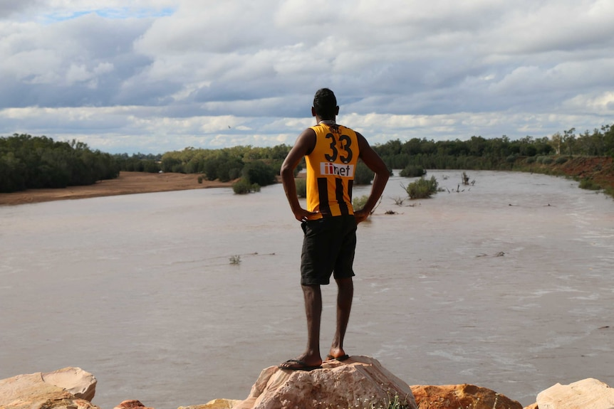 A young man looks out over the Fitzroy River in the Kimberley