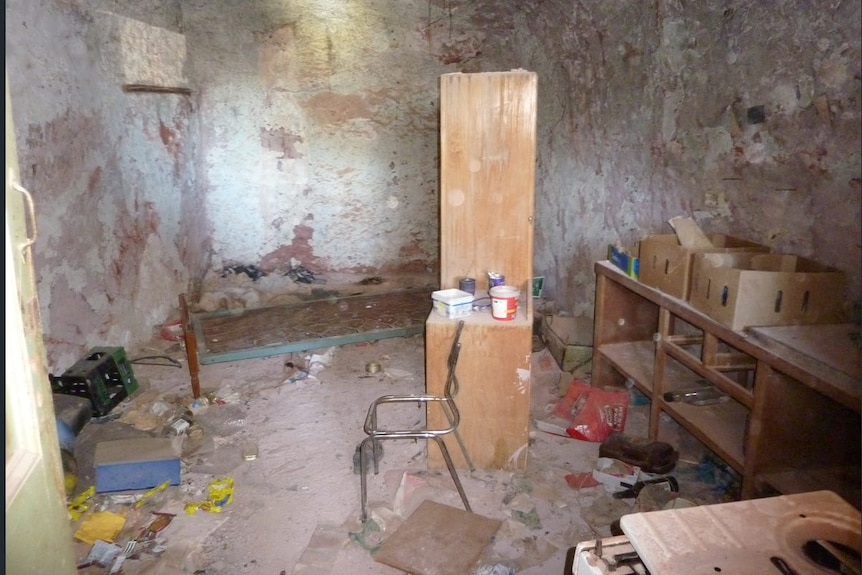 An interior shot of a vacant dugout with a dusty chair, cupboard, shelves and debris on the ground