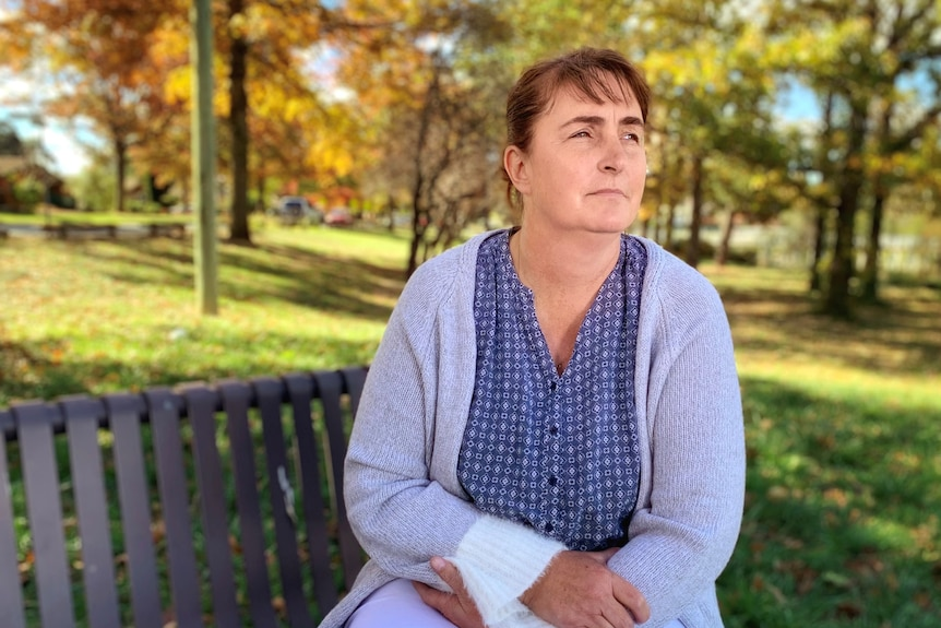 A woman sits on a park bench, looking pensively off into the distance.