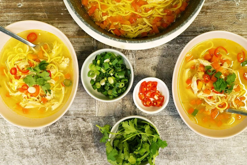 Two bowls of chicken noodle soup on a table with bowls of chilli, spring onion and corianders illustrating our simple recipe