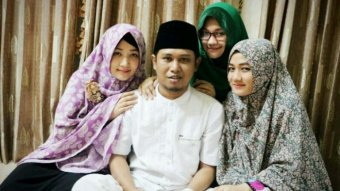 One of Indonesia's most well-known polygamists, Fadil Muzakki Syah, surrounded by his three wives, Siti, Yeni and Novita.