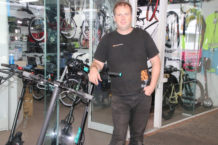 Anthony Van Duyn from Cairns Electric Bikes standing out front of his shop with several scooters