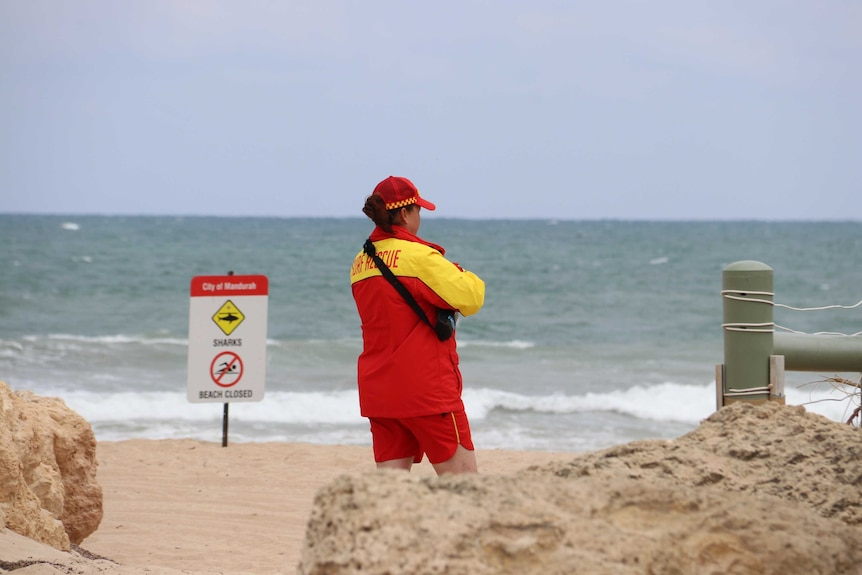 A surf lifesaver at Pyramids Beach stares at the ocean.