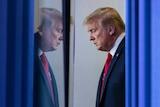 Donald Trump waiting behind a blue curtain looking serious