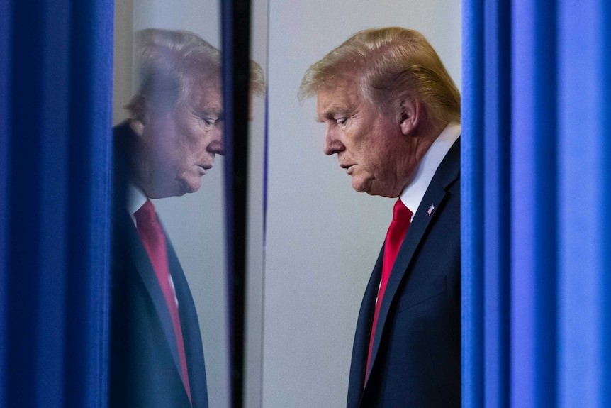 Donald Trump waiting behind a blue curtain looking serious