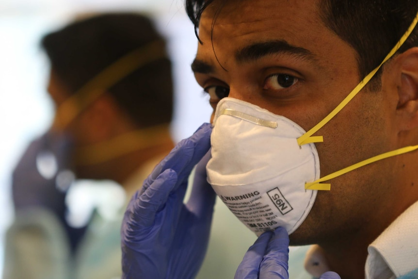 Melbourne GP Vyom Sharma looks into the camera while wearing a facemask.