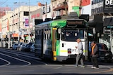 Two people walk across an intersection in front of a tram on a suburban street.