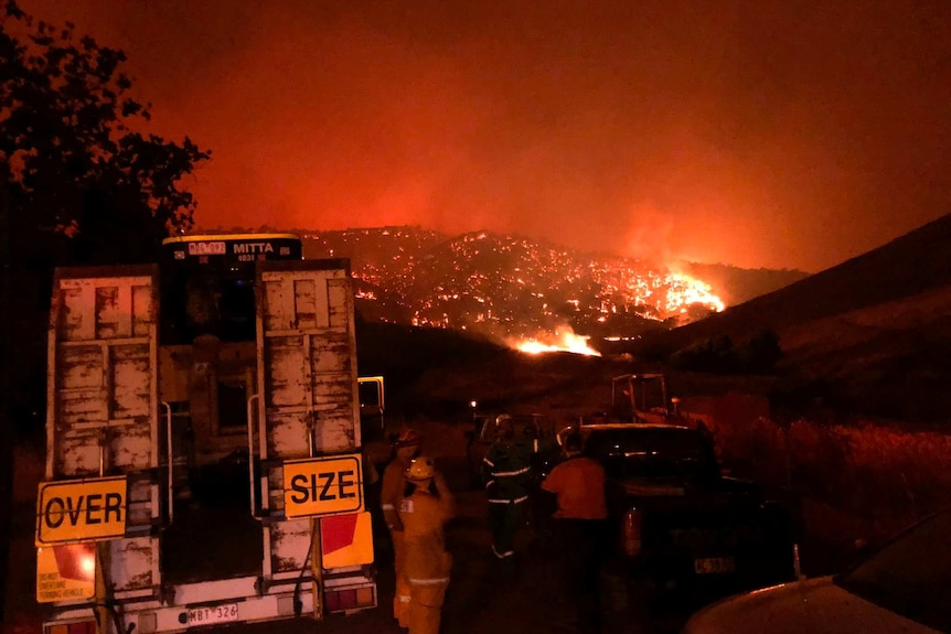 Firefighters gather in front of a mountain that is aglow with flames, near Corryong and Walwa.