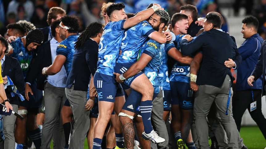 Three Blues Super Rugby trans-Tasman players embrace after beating the Highlanders.