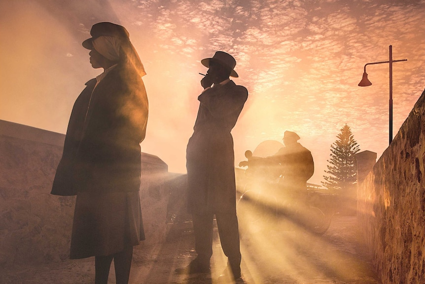 Gloss photo of individuals standing in sunlight.