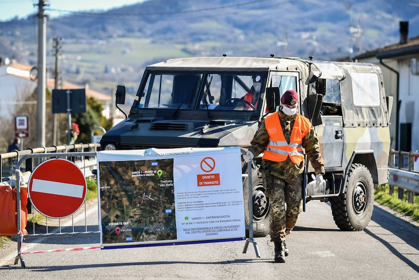 A soldier wearing a mask lifts up a barrier in front of an army truck with a rugged hill in background.