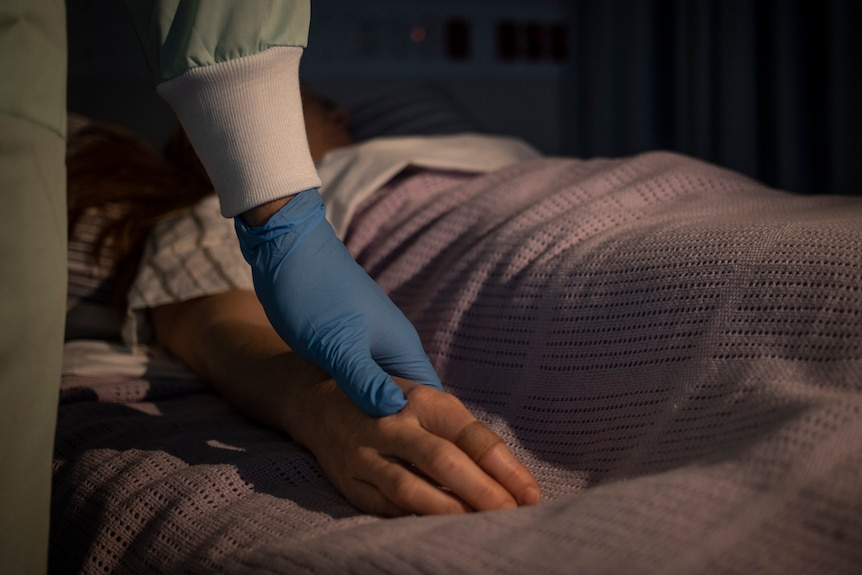 A gloved hand resting on a girl's hand in a hospital