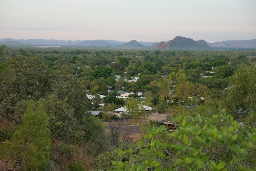 An aerial shot of an outback town with ranges behind it.