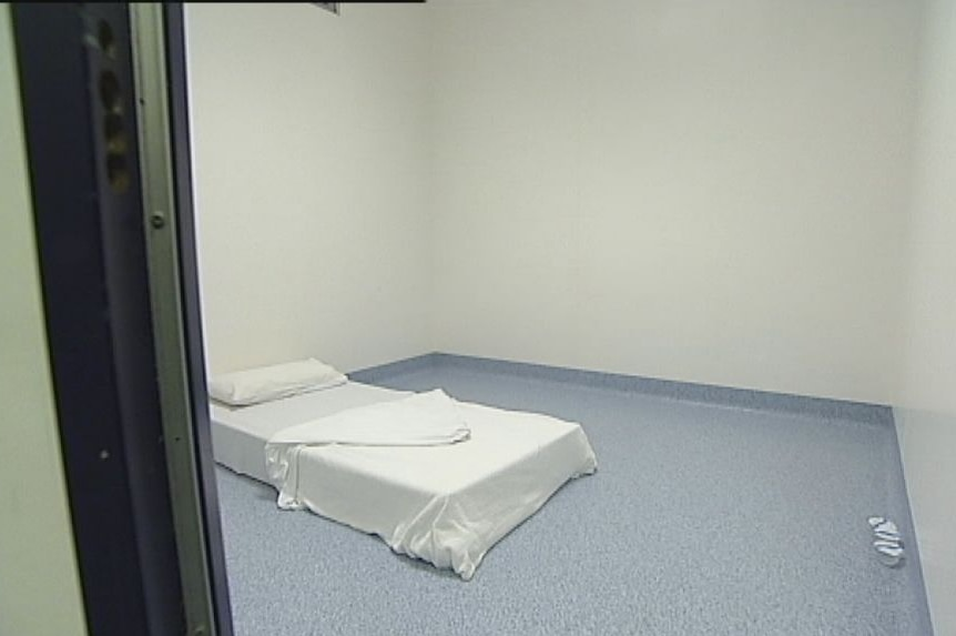 A plain white mattress with a white sheet on a linoleum-looking floor in a room with bare grey walls.