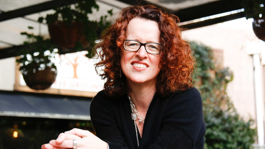 A portrait of Professor Genevieve Bell, smiling and sitting in a leafy cafe.