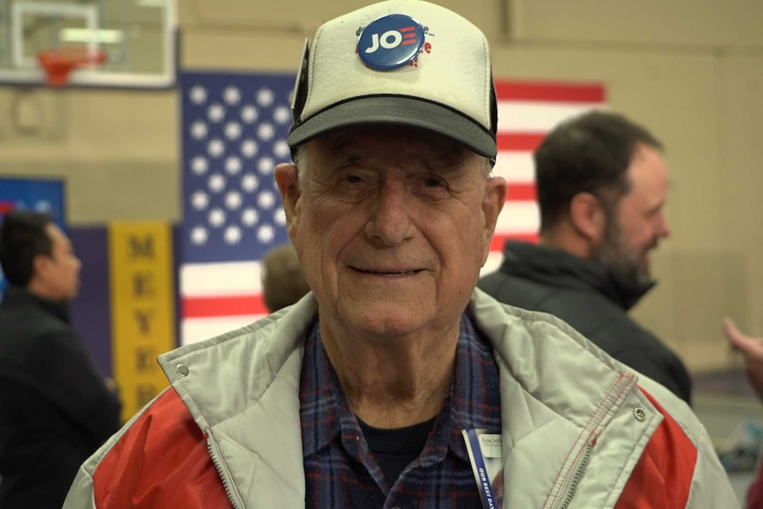 A man in a cap with a 'Joe' button attached to the front