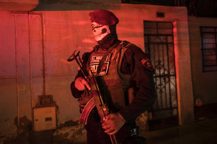 A police officer wearing combat gear, a beret and a bandana with the image of a skull on it stands guard in red street light.