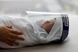 A newborn baby wears a protective face shield at a hospital in Hanoi.