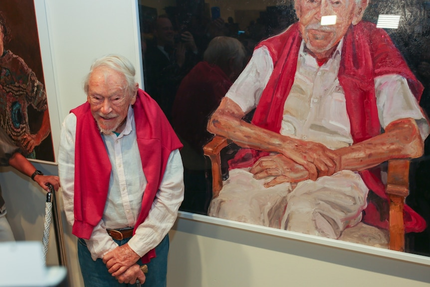 Guy Warren stands smiling next to a portrait of himself resting on his cane, wearing the same pink jumper around his shoulders