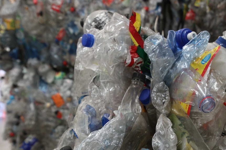 A close-up shot of crushed plastic bottles at a waste recovery centre.