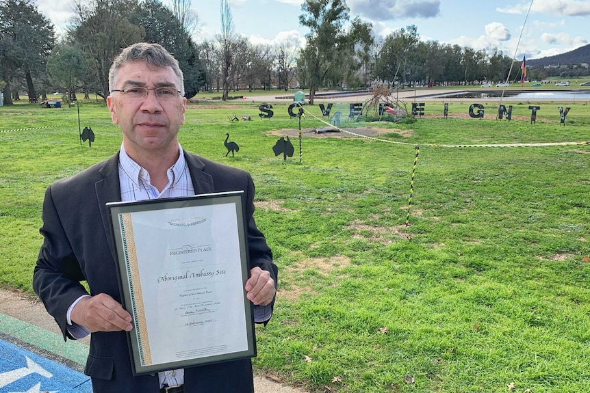 A man holds a certificate outside on a lawn.