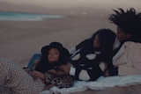 A screenshot from Janelle Monae's Dirty Computer. Janelle lies on a picnic blanket on the beach in between a man and a woman
