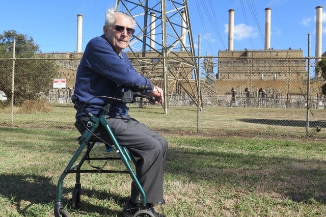 Reg sits on his walker's seat in front of the high fences containing the Hazelwood plant