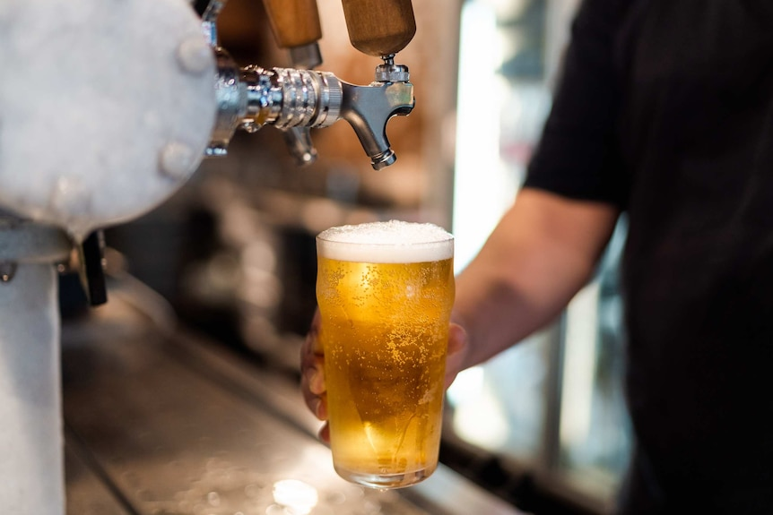 A close-up shot of a hand holding a full pint of beer below a beer tap after pouring it at a bar in a pub.