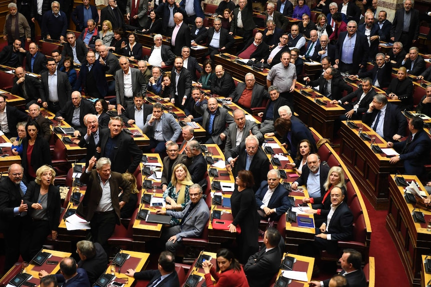 Dozens of Greek parliamentarians sit in parliament and are looking to the left