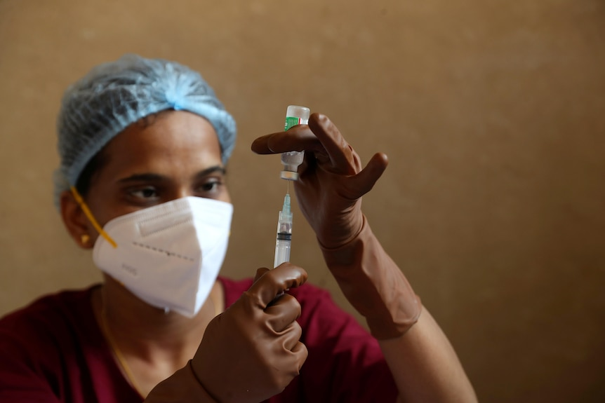 A health worker fills a syringe with a vial of COVID vaccine