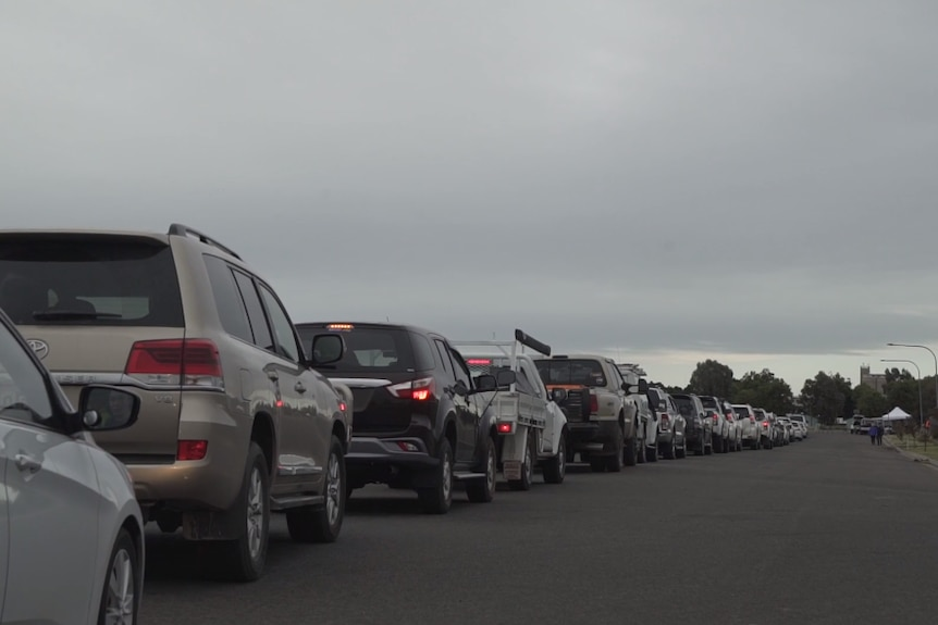 A long line of cars on a road leading to a small white tent.