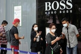 People wearing protective face masks stand in line to scan a barcode before entering a shopping mall.