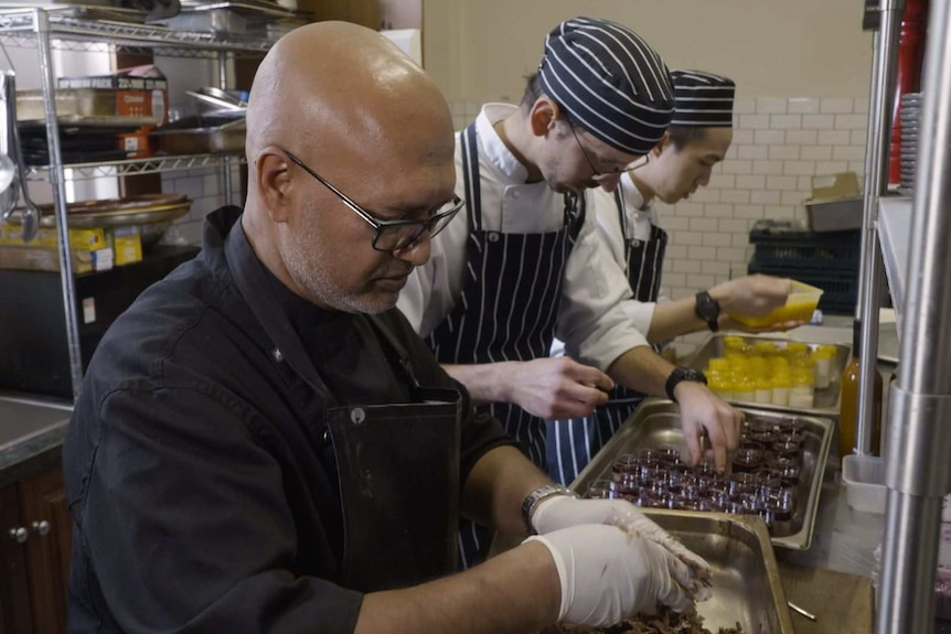 Bald man wearing glasses with 2 hatted young men behind him, in a kitchen preparing food