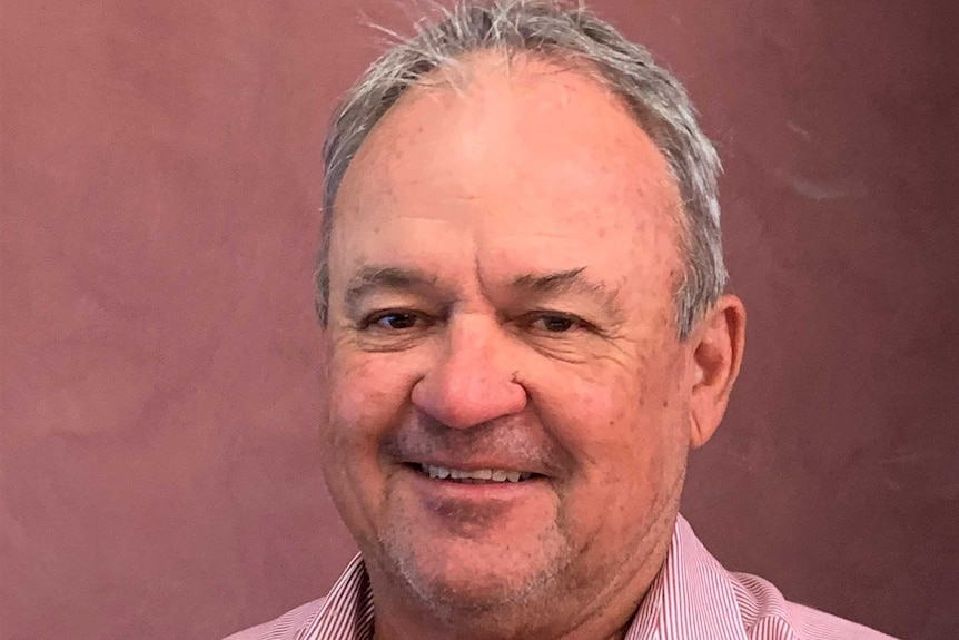 An older man with thinning grey hair, smiling for a portrait shot.