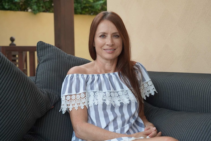A woman with red hair and green eyes wearing a grey and white striped dress smiles on a couch.