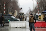 Security forces inspect the site of a suicide bombing in the diplomatic area of capital Kabul